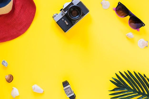 Vista elevada del sombrero; cámara; gafas de sol; conchas marinas; muñeca y hoja de palma en superficie amarilla.