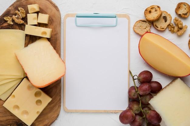 Vista elevada de la tabla de quesos; nuez; uvas rojas y rebanada de pan con portapapeles vacío