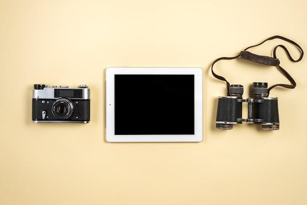 Una vista elevada de la tableta digital con cámara retro y binoculares sobre fondo beige