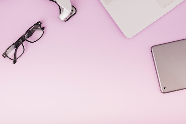 Vista elevada de la tableta digital; gafas y portátil sobre fondo rosa