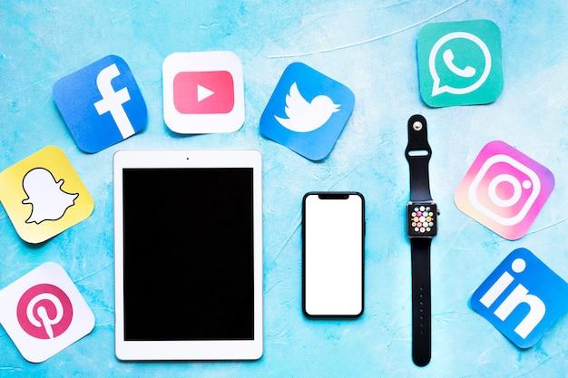 Vista elevada de tableta digital, teléfono móvil y reloj inteligente con recortes de iconos de aplicaciones