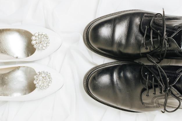 Una vista elevada de tacones blancos y zapatos negros en bufanda