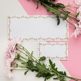 Vista elevada de la tarjeta en blanco con flores frescas sobre fondo dual