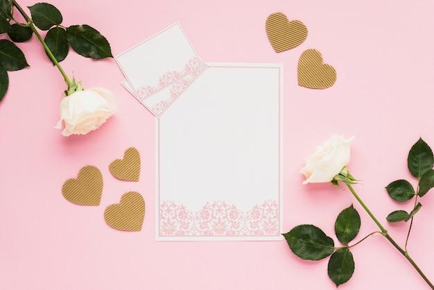 Vista elevada de tarjetas en blanco con corazones dorados y rosas en superficie rosada