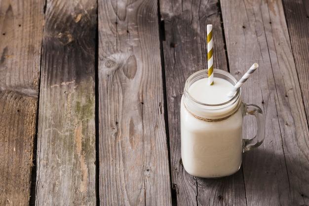 Vista elevada del tarro de leche con dos pajas de beber en la mesa de madera