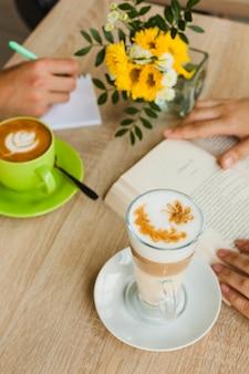 Vista elevada de la taza de café y el café con leche cerca de las personas que estudian en cafés