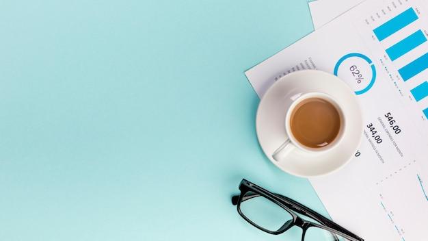 Una vista elevada de la taza de café en el plan de presupuesto de negocios y anteojos sobre fondo azul