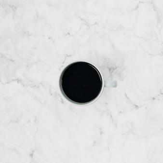 Una vista elevada de la taza de café sobre el telón de fondo con textura de mármol