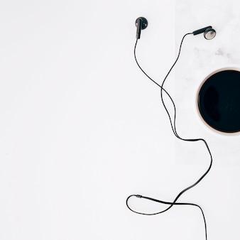 Una vista elevada de la taza negra del auricular y de café en el fondo blanco