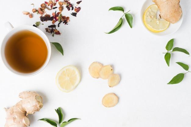 Una vista elevada de la taza de té de hierbas con limón; jengibre y hierbas secas sobre fondo blanco