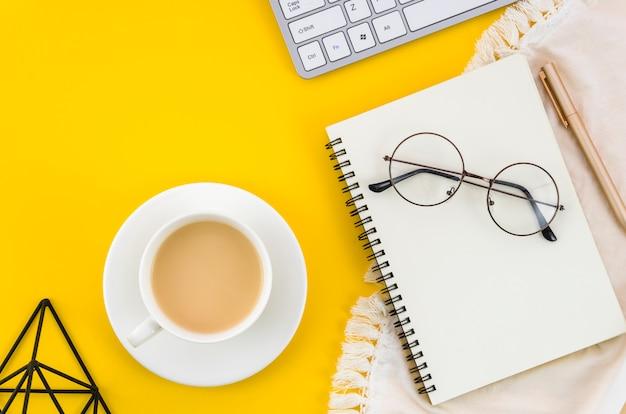 Una vista elevada de la taza de té y el platillo con anteojos; bloc de notas de espiral un anteojos sobre fondo amarillo