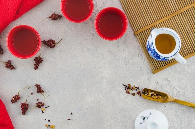 Una vista elevada de tazas de cerámica rojas y té de hierbas en una jarra sobre fondo con textura
