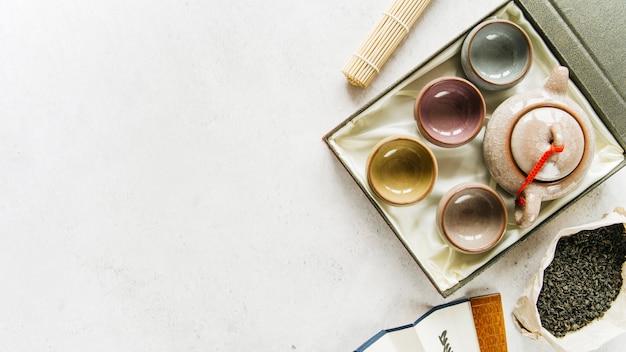Una vista elevada de tazas de té de cerámica china y tetera con hojas de té secas sobre fondo de hormigón