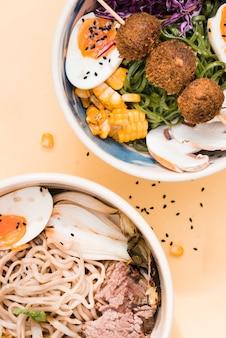 Una vista elevada de tazones de fideos asiáticos tradicionales sobre fondo beige