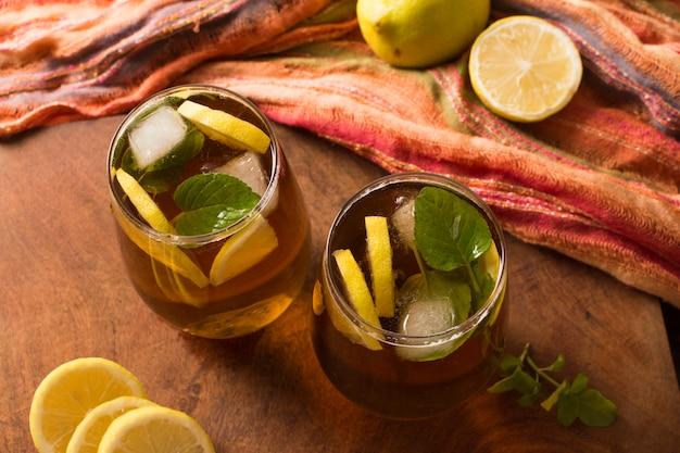 Una vista elevada de té helado de limón y hojas de menta en mesa de madera