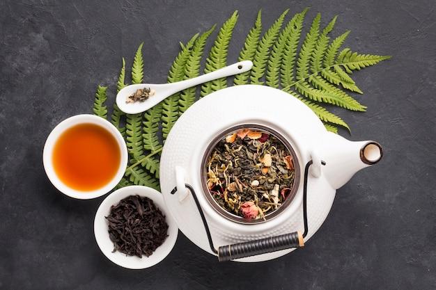 Vista elevada de té de hierbas e ingredientes saludables con hojas de helecho sobre fondo negro de pizarra