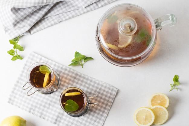 Una vista elevada de té de limón y menta sobre fondo blanco
