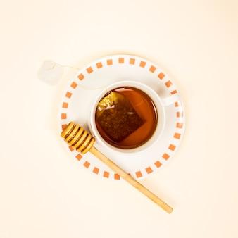 Vista elevada de té saludable con cucharón de miel