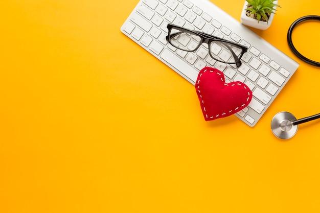 Vista elevada del teclado inalámbrico; gafas; planta suculenta; con juguete de tela cosida sobre fondo amarillo