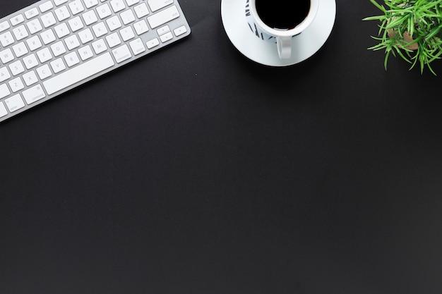 Una vista elevada del teclado; taza de café; y maceta sobre fondo negro con espacio de copia