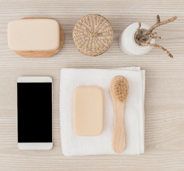 Vista elevada del teléfono inteligente; jabón; cepillo; toalla y cesta de mimbre sobre fondo de madera.