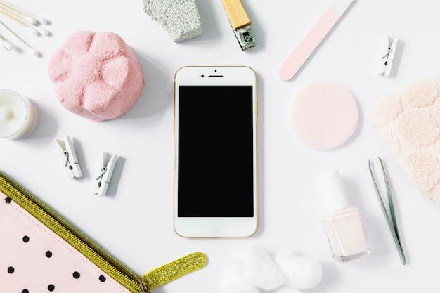 Vista elevada del teléfono inteligente rodeado de varios productos de spa en superficie blanca