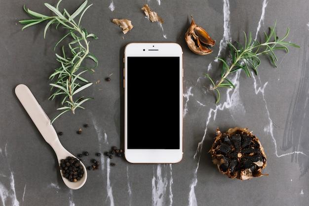 Vista elevada del teléfono inteligente; romero; pimienta negra y ajo