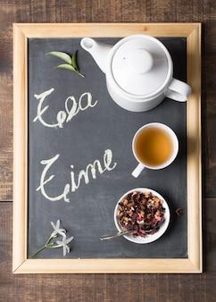 Una vista elevada de la tetera; taza de té de limón y hierbas secas con hojas y flores en la pizarra