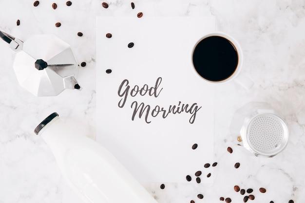 Una vista elevada del texto de buenos días sobre papel; cafetera cafetera; taza de café; botella de leche y granos de café sobre fondo de mármol