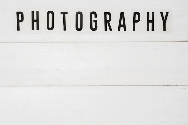 Vista elevada de texto de fotografía sobre mesa de madera blanca