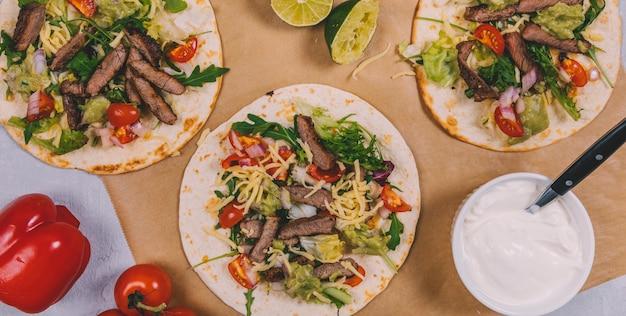 Vista elevada de las tiras de carne mexicana con verduras en tortilla