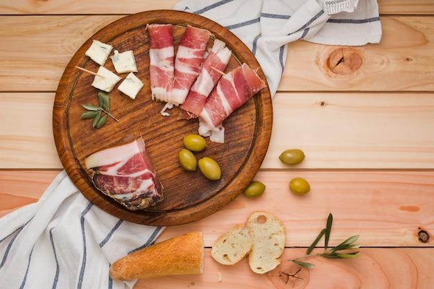 Una vista elevada de tocino; olivos; rebanadas de queso y pan en tablero circular de madera sobre la mesa