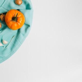Vista elevada de tomate; cebolla y ajo en superficie blanca.