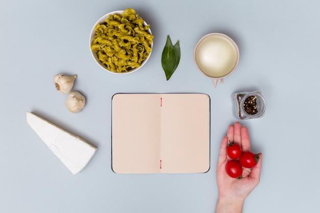 Vista elevada de tomate cherry rojo con ingrediente de pasta y cuaderno abierto