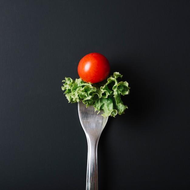 Vista elevada de tomate fresco y lechuga con tenedor en superficie negra