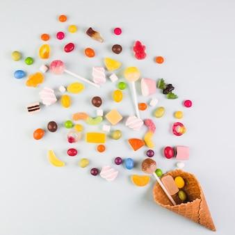 Vista elevada de varios caramelos con cono de waffle de helado sobre fondo blanco