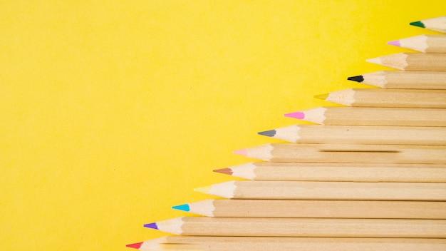 Vista elevada de varios lápices de colores sobre fondo amarillo