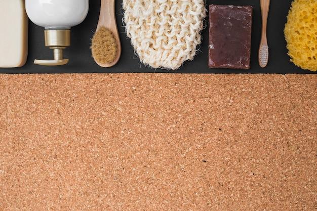Vista elevada de varios productos cosméticos sobre fondo de corcho