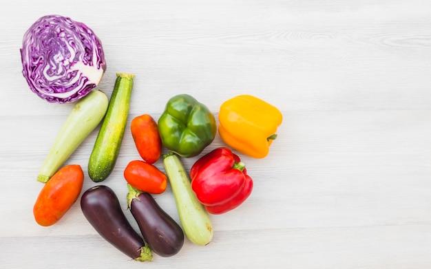 Vista elevada de verduras crudas saludables sobre fondo de madera