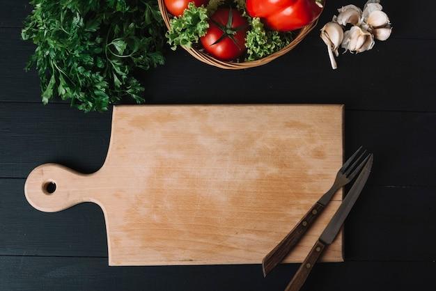 Vista elevada de verduras frescas; dientes de ajo; tabla de cortar y utensilios para comer sobre fondo negro
