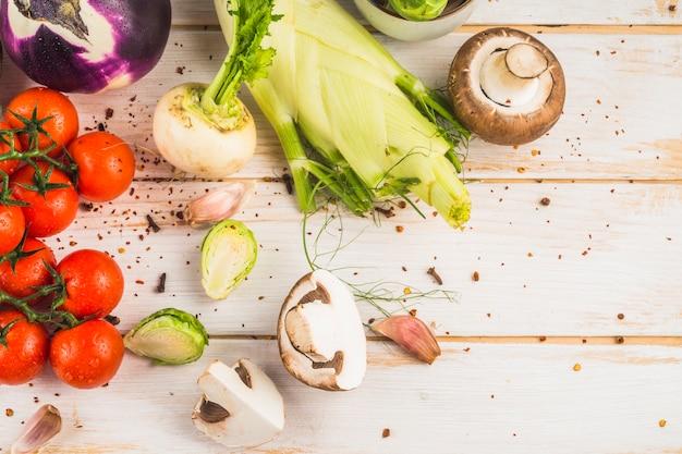 Vista elevada de verduras frescas y hojuelas de chile sobre fondo de madera