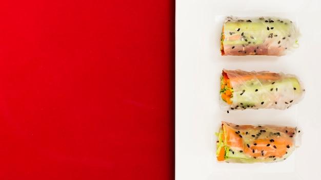 Una vista elevada de verduras frescas y salmón pescado rollitos de primavera en la placa