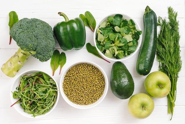 Una vista elevada de verduras frescas saludables; frijol mungo y manzana en mesa blanca