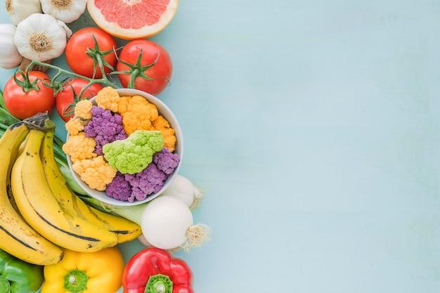 Vista elevada de verduras y frutas sobre fondo azul