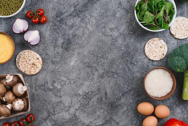 Una vista elevada de las verduras; huevos y pastel de arroz inflado sobre fondo de hormigón gris