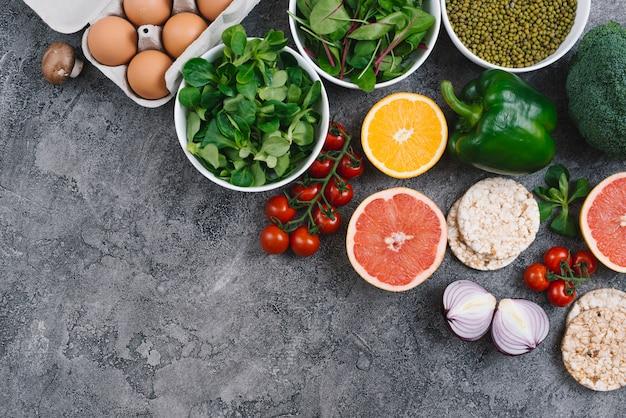 Una vista elevada de las verduras; huevos; pastel de cítricos y arroz inflado sobre fondo de hormigón gris