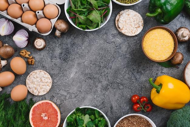 Una vista elevada de las verduras; nueces pastel de frutas y arroz inflado sobre fondo de hormigón gris