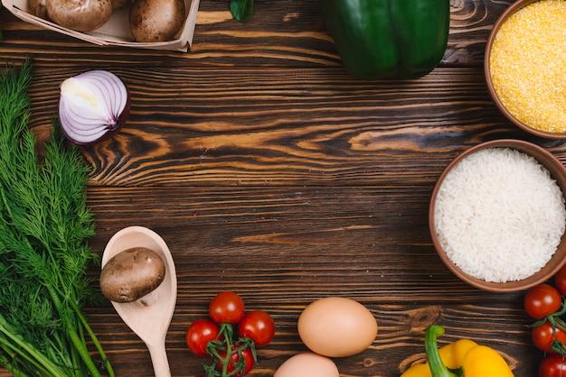 Una vista elevada de verduras con un tazón de granos de arroz y polenta en mesa de madera