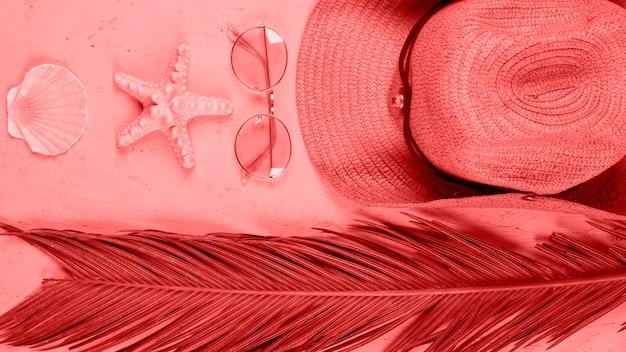 Una vista elevada de vieira; estrella de mar; gafas de sol; sombrero y hojas de palma sobre fondo coral