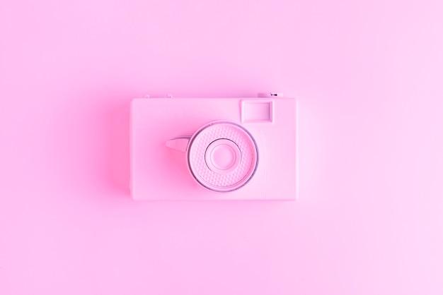 Una vista elevada de la vieja cámara vintage sobre superficie rosa